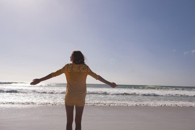Kvinnaanseende med armar som är utsträckta på stranden fotografering för bildbyråer