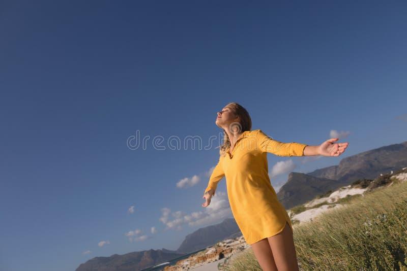 Kvinnaanseende med armar som är utsträckta på stranden royaltyfri foto
