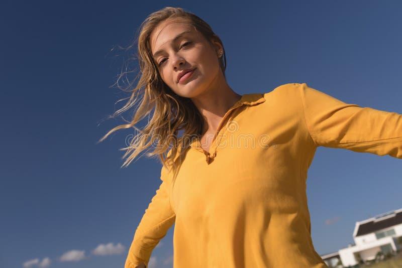 Kvinnaanseende med armar som är utsträckta på stranden arkivfoto