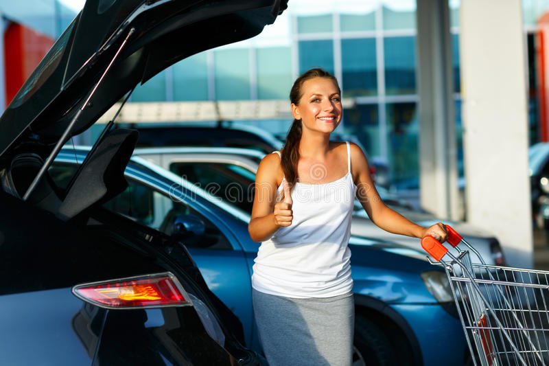 Kvinnaanseende med den shoppingvagnen och tummen upp nära bilen på t royaltyfria bilder