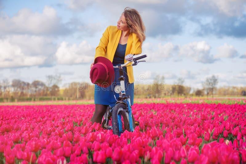 Kvinnaanseende med hennes cykel i tulpanfält fotografering för bildbyråer