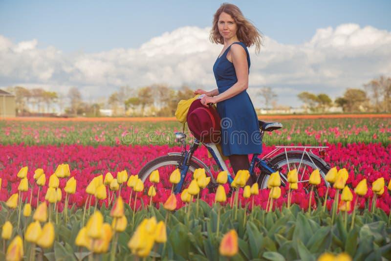 Kvinnaanseende med hennes cykel i tulpanfält royaltyfri bild