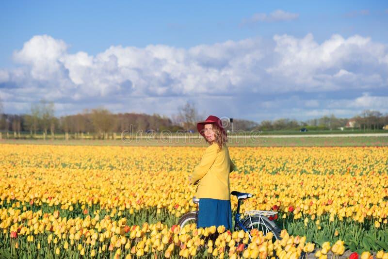 Kvinnaanseende med hennes cykel i tulpanfält arkivbild