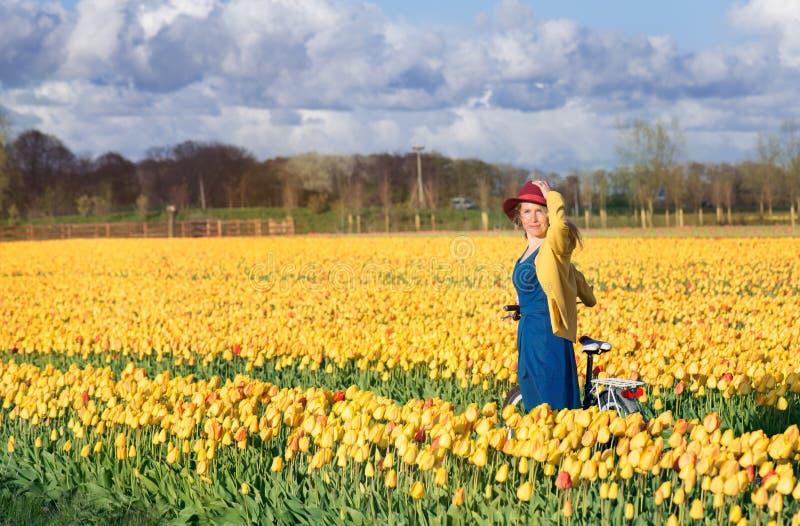 Kvinnaanseende med hennes cykel i tulpanfält royaltyfri foto