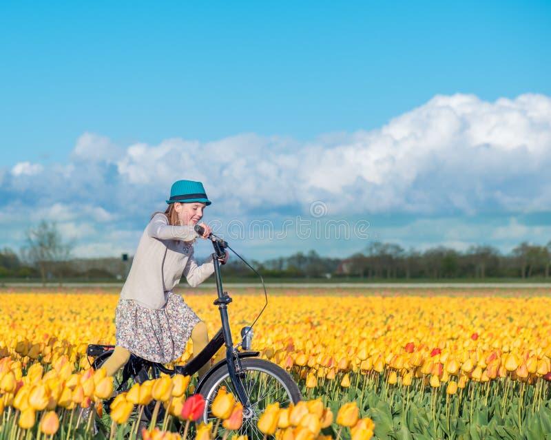 Kvinnaanseende med hennes cykel i tulpanfält arkivfoton
