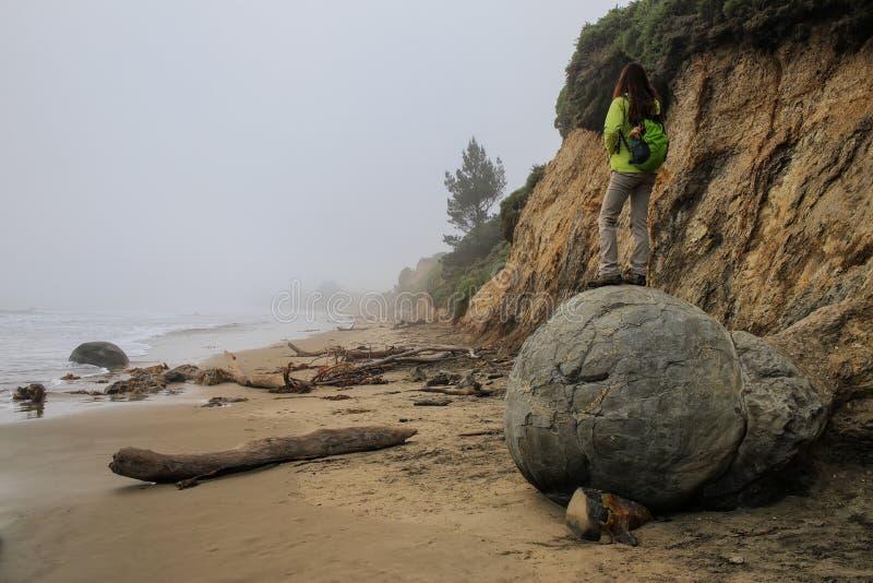 Kvinnaanseende på den Moeraki stenblocket på den Koekohe stranden, Otago, södra ö, Nya Zeeland royaltyfria foton