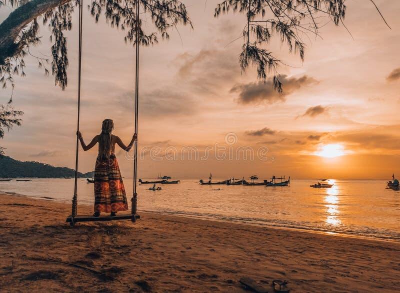 Kvinnaanseende på en gunga på stranden i Thailand, Koh Tao hållande ögonen på solnedgång arkivfoto