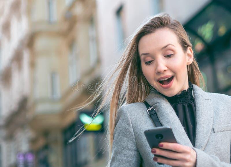 Kvinnaanseende på gatan och användamobiltelefonen arkivbilder
