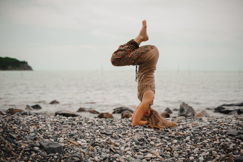 Kvinnaanseende på hennes head görande yoga royaltyfri fotografi