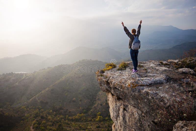 Kvinnaanseende på klippan med utsträckta armar arkivfoto