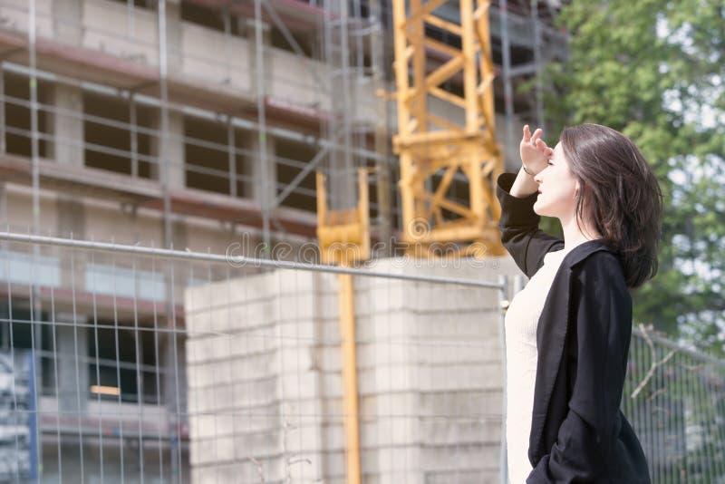 Kvinnaanseende på konstruktionsplatsen och se byggnad royaltyfria foton