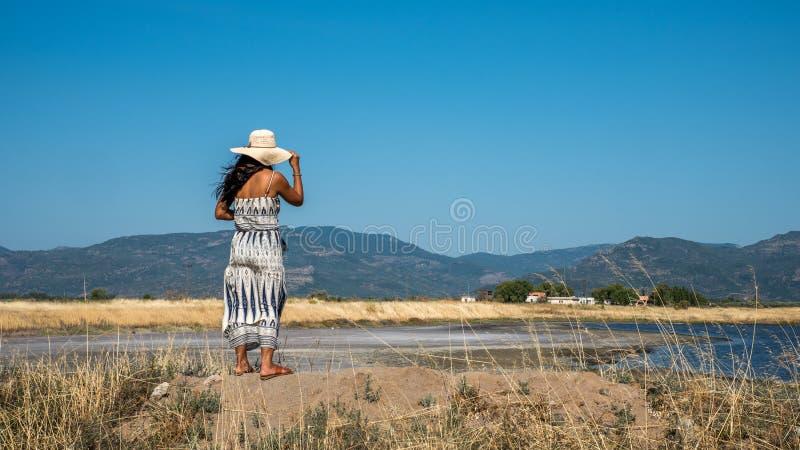 Kvinnaanseende på kulleinnehavhatten och se byn i dis arkivbild