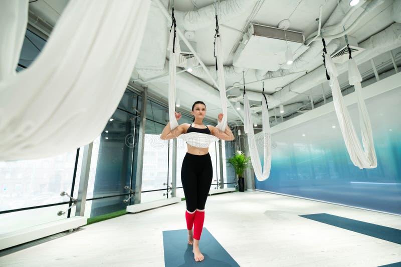 Kvinnaanseende på mattt, innan övning av flyg- yoga royaltyfria bilder
