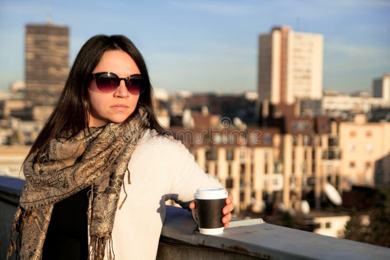Kvinnaanseende på taket, hållande kaffe som tänker och ser royaltyfria foton