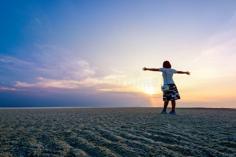 Kvinnaanseendet beväpnar utsträckt på solnedgången arkivfoto