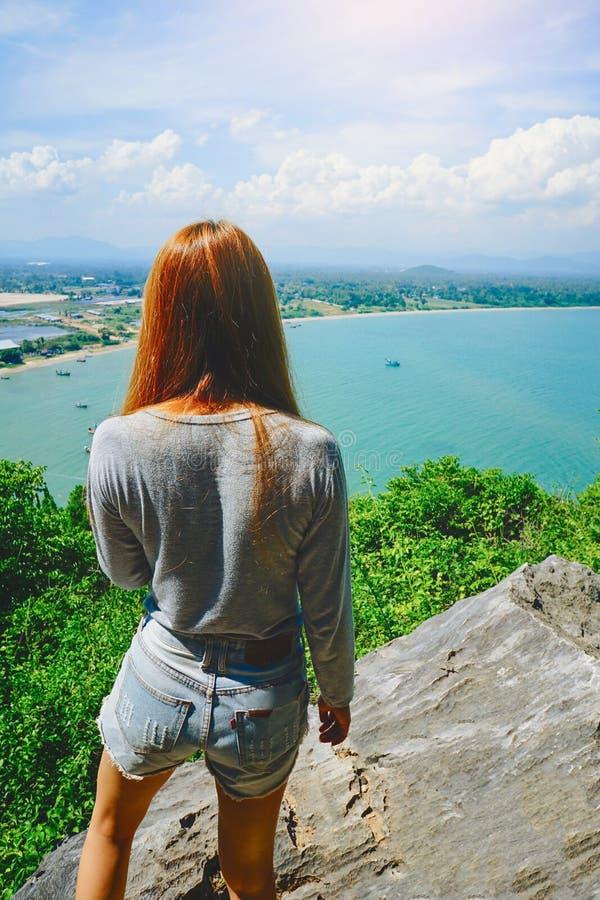 Kvinnaanseendet på klippan och ser något på den blåa himlen, det blåa havet och molnet arkivbild