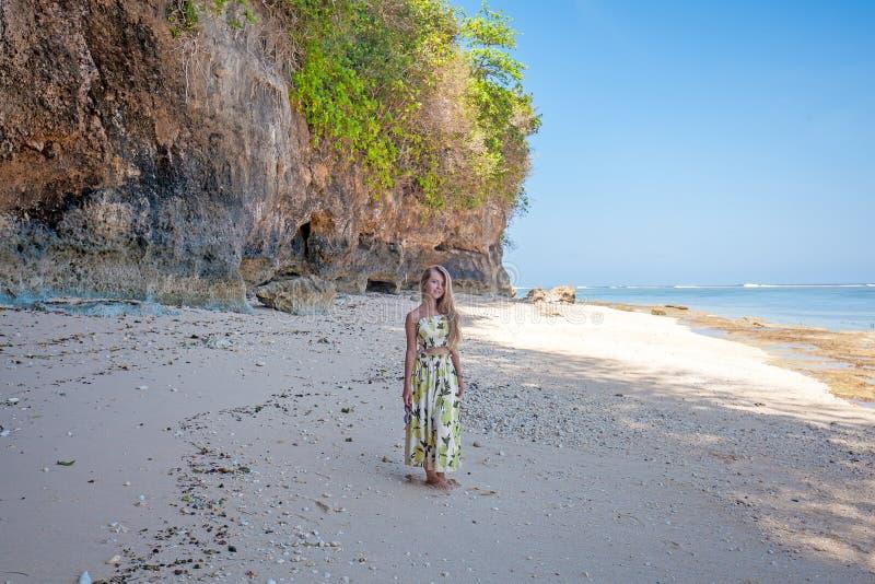 Kvinnaanseendet på stranden nära vaggar och havet fotografering för bildbyråer