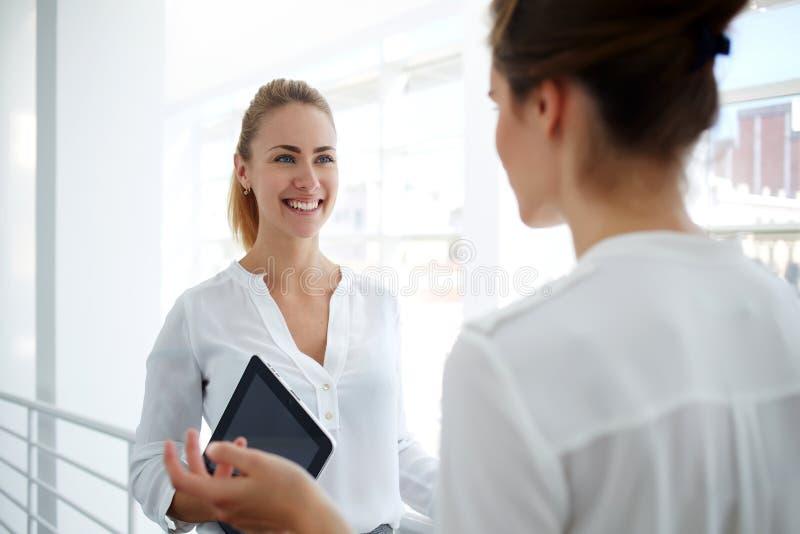 Kvinnaanställd som konsulterar med mer kompetent chef som hållande digital minnestavla om arbetsplan under avbrott, royaltyfri bild