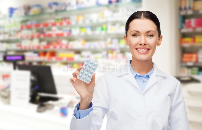 Kvinnaapotekare med preventivpillerapoteket eller apotek arkivbilder