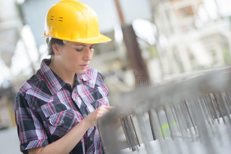 Kvinnaarbetare med hjälmen över vit i fabrik arkivfoton