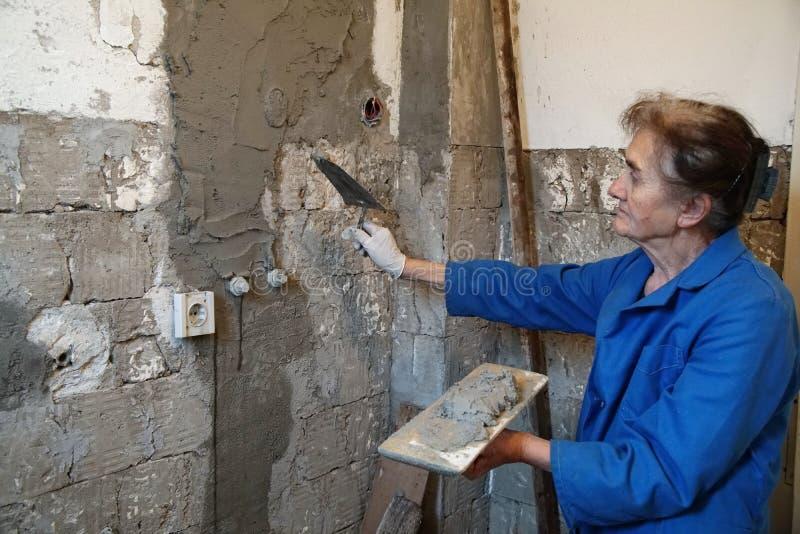 Kvinnaarbetare som rappar betong på väggen av huset royaltyfri bild