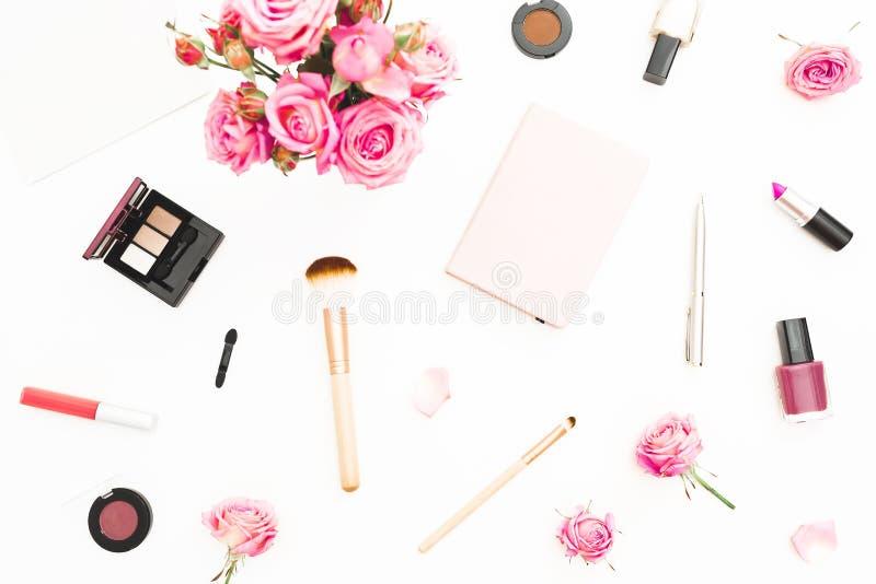 Kvinnaarbetsutrymme med rosa rosor, skönhetsmedel, dagbok på vit bakgrund Top beskådar Lekmanna- hem- kvinnligt skrivbord för läg royaltyfria foton