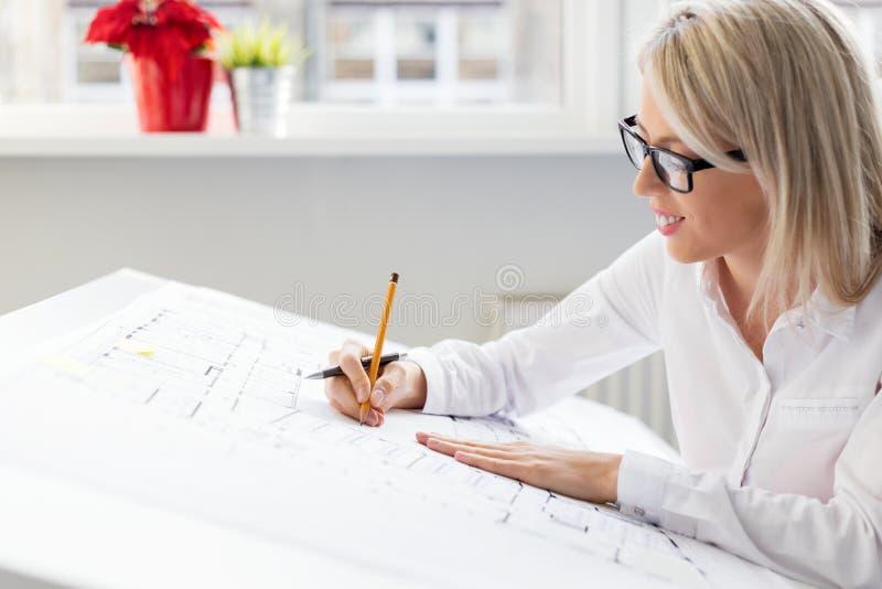 Kvinnaarkitekt som arbetar på arkitektoniska ritningar royaltyfri fotografi
