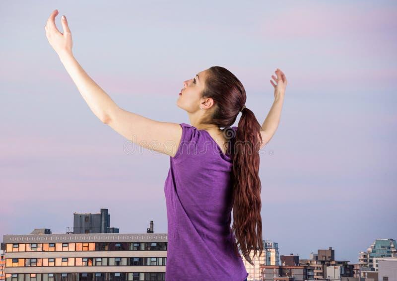 Kvinnaarmar i luft mot byggnader och aftonhimmel royaltyfria foton