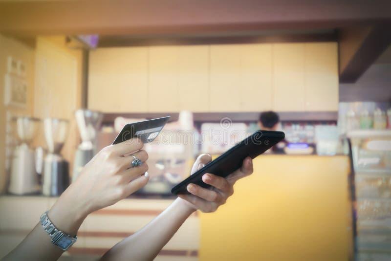 kvinnaasiat som använder den smarta telefonen, och kreditkort som direktanslutet shoppar, arkivbild