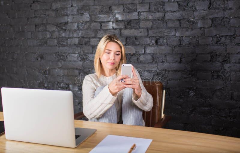 Kvinnaavståndsarbetare som pratar i socialt nätverk på mobiltelefonen under arbete på bärbar datordatoren royaltyfri bild