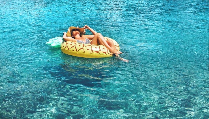 Kvinnabad på uppblåsbar ananas ringer utom fara havsvatten arkivbild