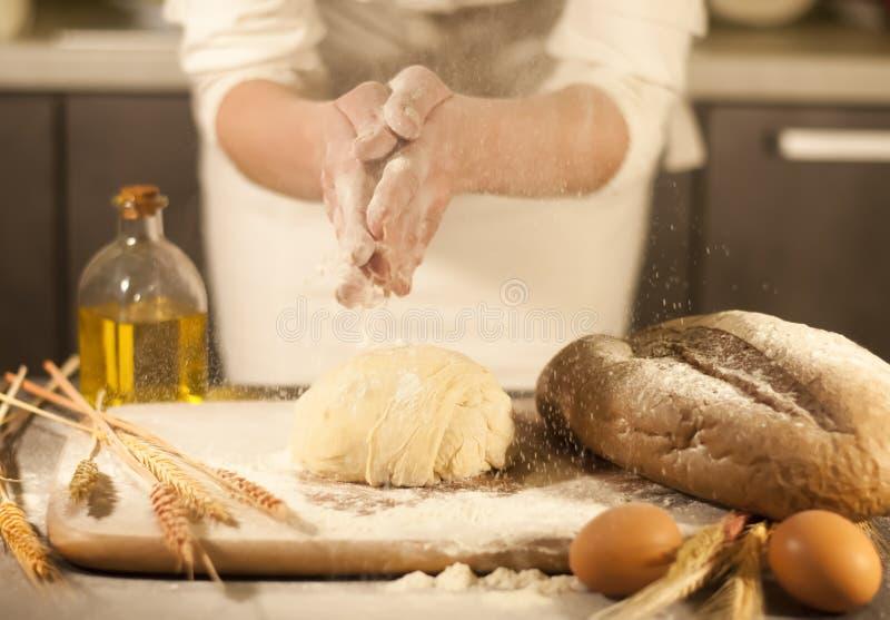Kvinnabagaren räcker blandande recept som knådar smör, tomatförberedelsedeg och gör bröd royaltyfria foton