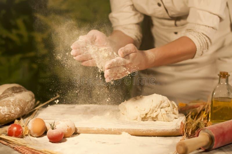 Kvinnabagaren räcker blandning, recept som knådar smör, tomatförberedelsedeg och gör bröd royaltyfri fotografi