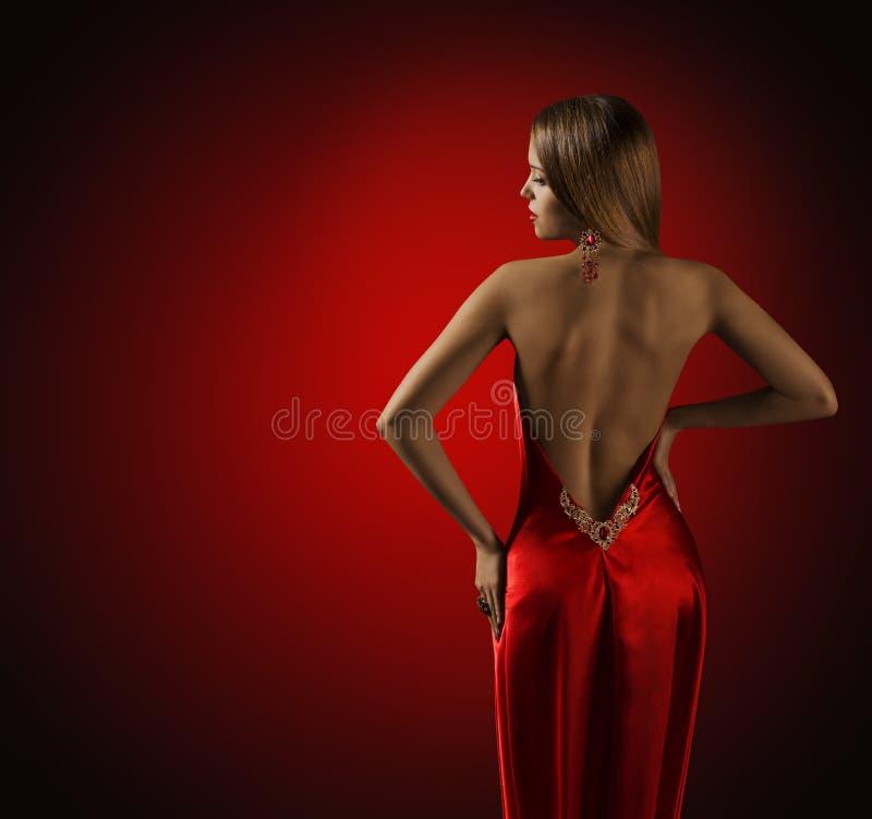 Kvinnabaksida i den röda klänningen, härlig modemodell Rear View arkivfoton