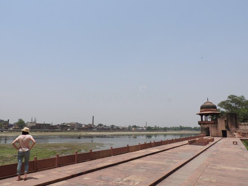 Kvinnabaksidasikten, vänder mot inte synligt och att beundra gravvalvet av Itimad-UD-Daul, lilla Taj Mahal, Agra, Indien royaltyfri fotografi