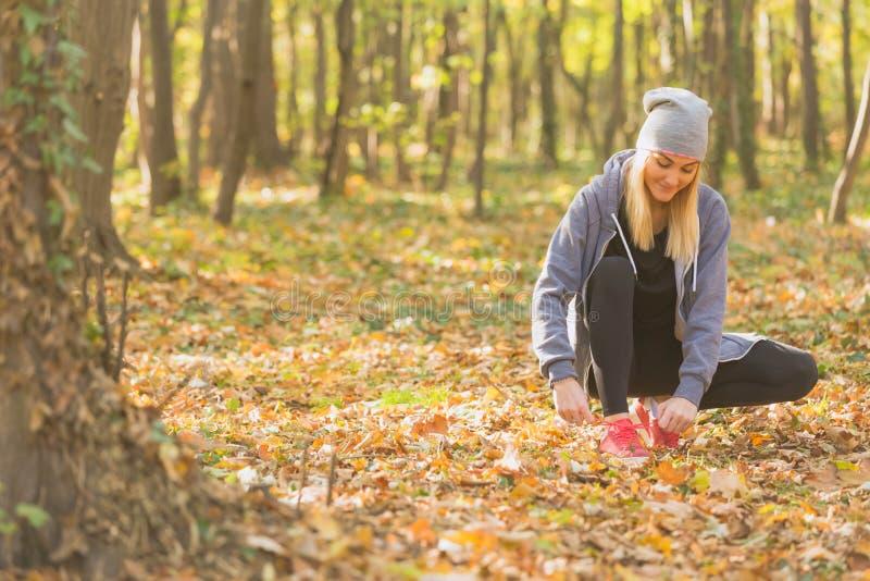 Kvinnaband snör åt av rinnande skor för utomhus- jogga Sportbegrepp royaltyfri fotografi