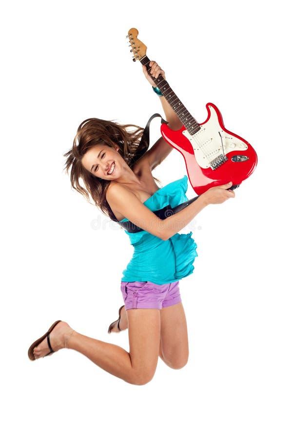 Kvinnabanhoppning med en elektrisk gitarr royaltyfri fotografi