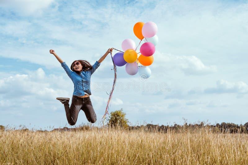 Kvinnabanhoppning med färgrika ballonger i ängen arkivfoton