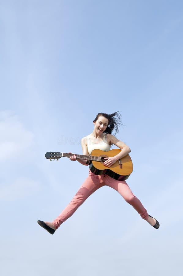 Kvinnabanhoppning med gitarren in i himlen arkivbilder