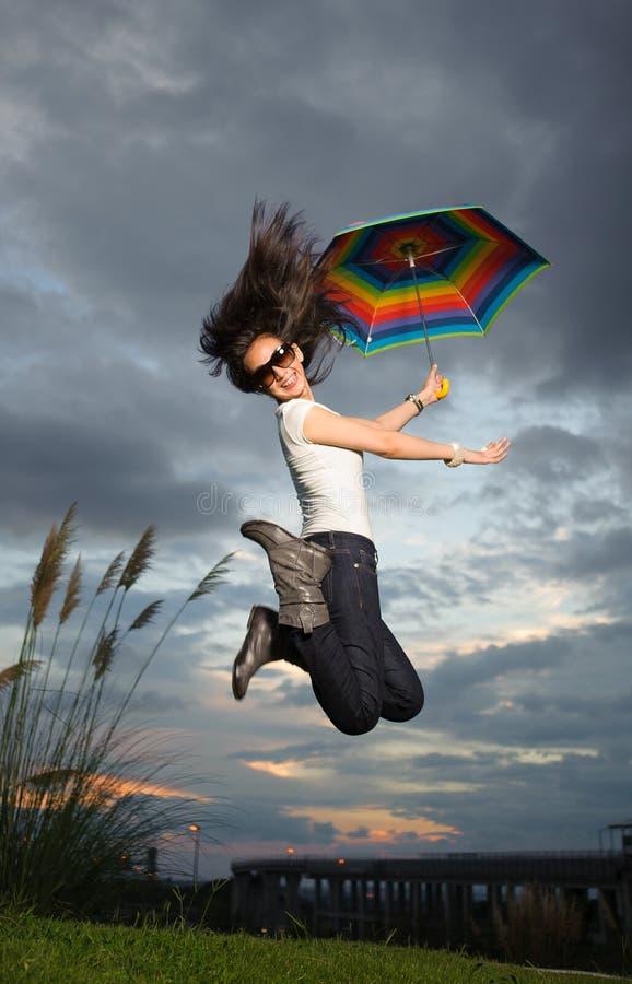 Kvinnabanhoppning med regnbågeparaplyet fotografering för bildbyråer