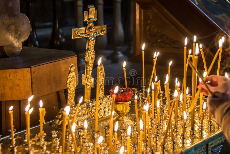 Kvinnabelysningstearinljus i kristen kyrka royaltyfri fotografi