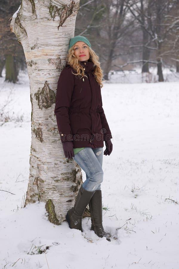 Kvinnabenägenhet mot träd i vinter arkivbilder