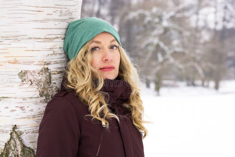Kvinnabenägenhet mot träd i vinter fotografering för bildbyråer