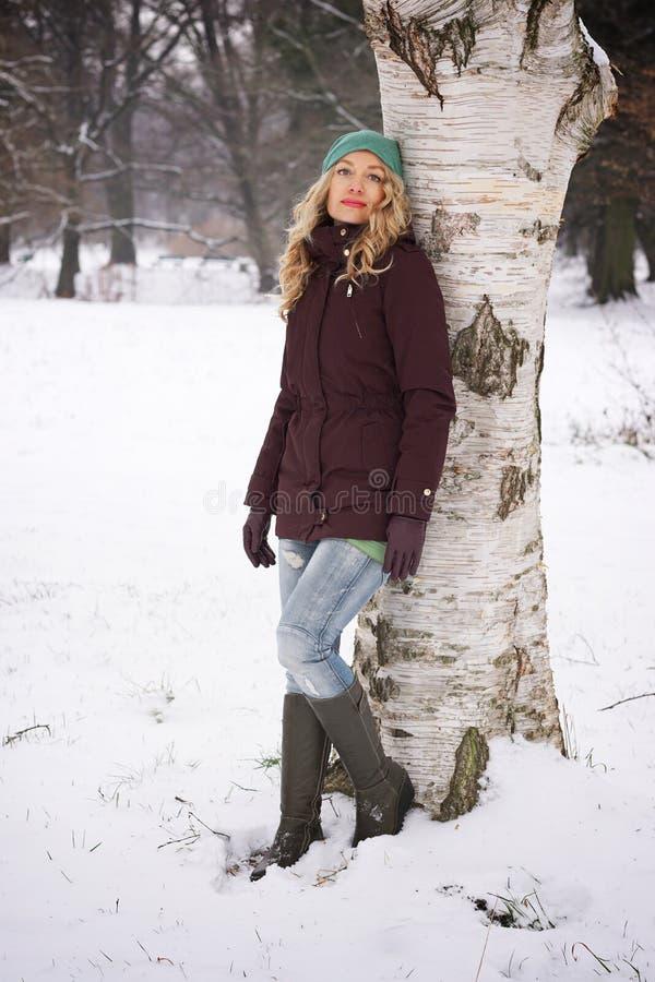 Kvinnabenägenhet mot träd i vinter royaltyfria foton