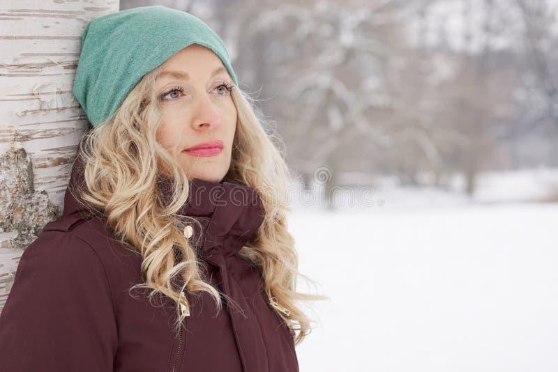 Kvinnabenägenhet mot träd i vinter arkivfoto