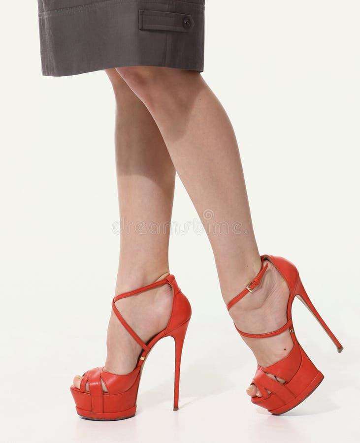 Kvinnaben i röda skor för höga häl arkivbilder