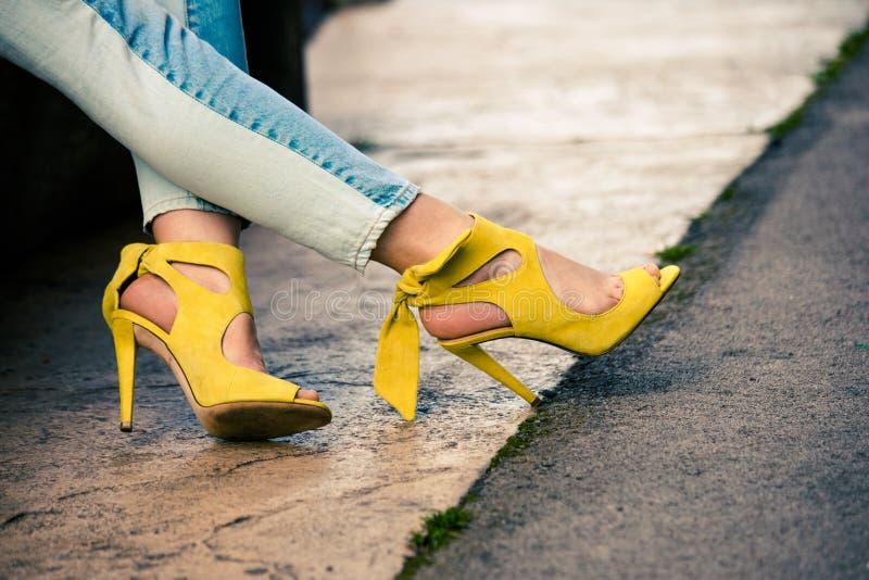 Kvinnaben i sandaler för hög häl för läderguling som är utomhus- i stad fotografering för bildbyråer