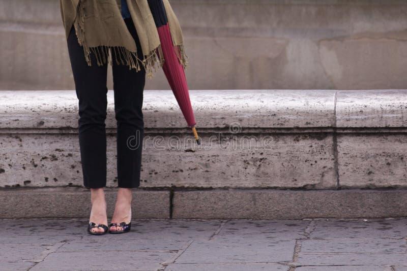 Kvinnaben med häl och paraplyet arkivbild