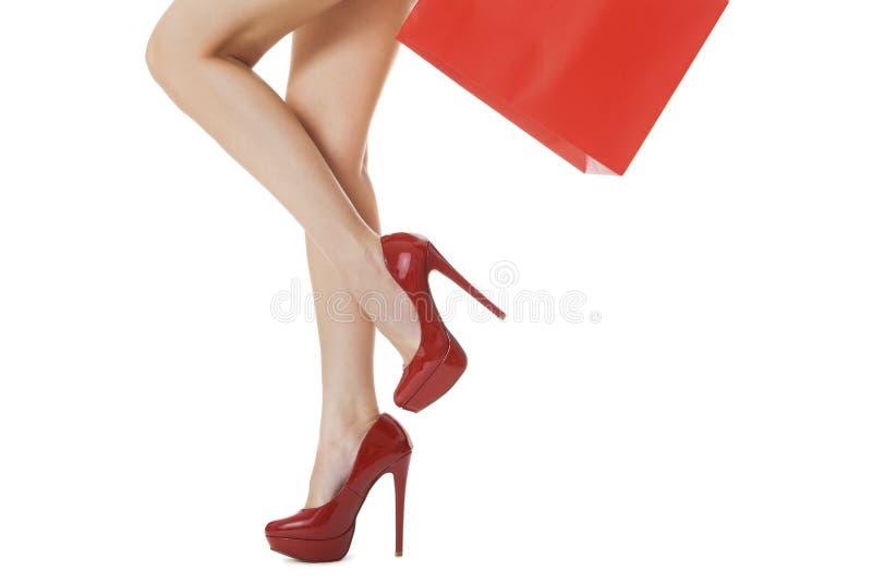 Kvinnaben med prickfri hud i röda höga häl arkivbilder