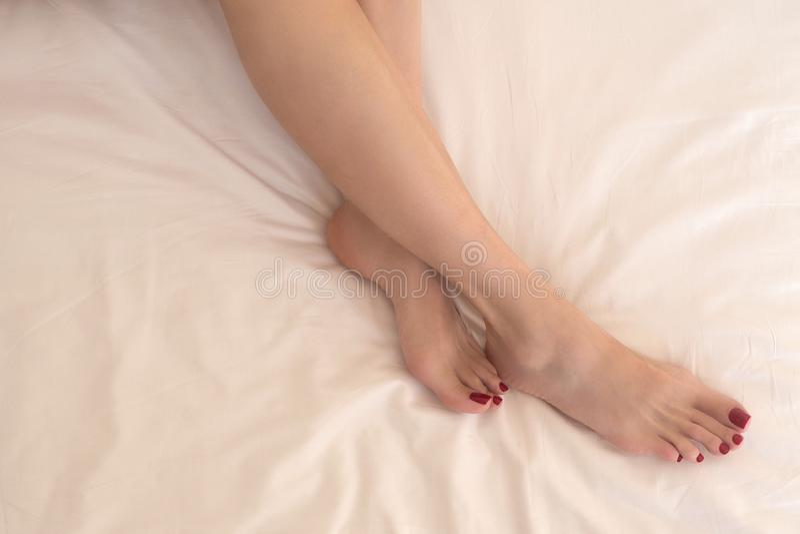 Kvinnaben med slät hud på vit sängkläder, slut upp royaltyfri foto